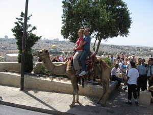 Kelli and Peter sitting on a camel with the Temple Mount in the background